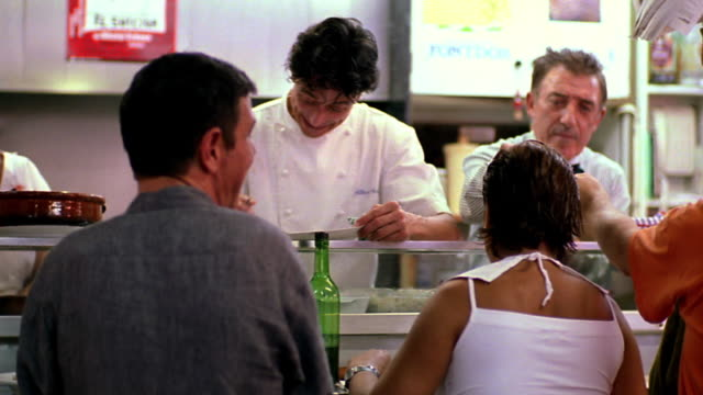 PAN waiters, waitresses + chef behind counter of restaurant / customers in foreground / Barcelona, Spain