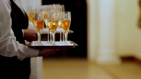 vídeos y material grabado en eventos de stock de plano medio de cerca los camareros con las flautas de champán en bandejas - less than 10 seconds