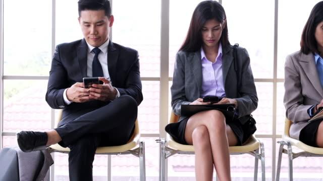 vidéos et rushes de en attente d'une entrevue. plan rapproché des gens d'affaires à l'aide de smartphone. - doigt humain