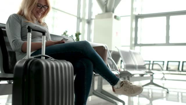 vídeos y material grabado en eventos de stock de esperando en la terminal del aeropuerto mediante teléfono - maleta