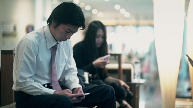 waiting people looking at phones - portability点の映像素材/bロール