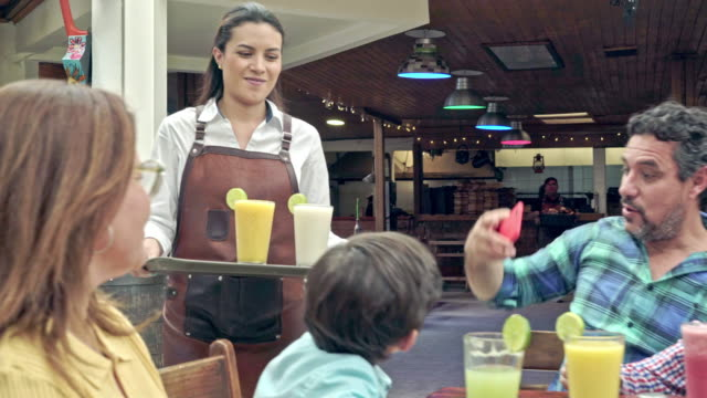 waitress arrives at the table where the family is with their drinks - 25 29 years stock videos & royalty-free footage