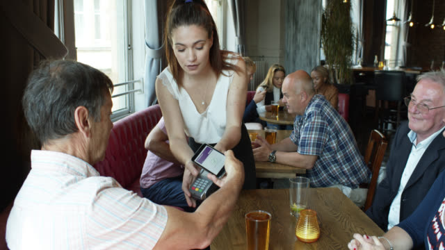 waitress bringing credit card machine to table in pub - contactless payment stock videos & royalty-free footage