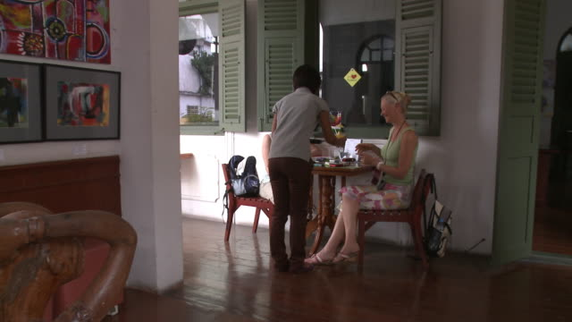 WS ZI CU Waitress bringing drinks to two women in cafe, Bangkok, Thailand