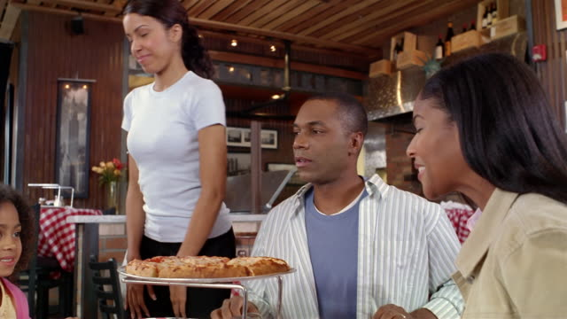 Waitress bringing pie to family at pizza restaurant / placing pie on tray stand / family taking slices