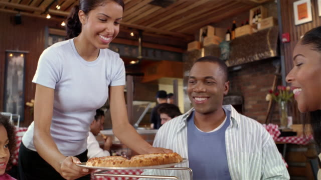 vídeos de stock, filmes e b-roll de waitress bringing pie to family at pizza restaurant / putting pizza on stand / family members lifting slices off tray and putting on plates - pie humano