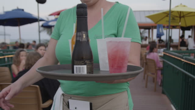 vídeos y material grabado en eventos de stock de a waitress carries a tray of drinks to customers sitting at tables on an outdoor patio. - camarero
