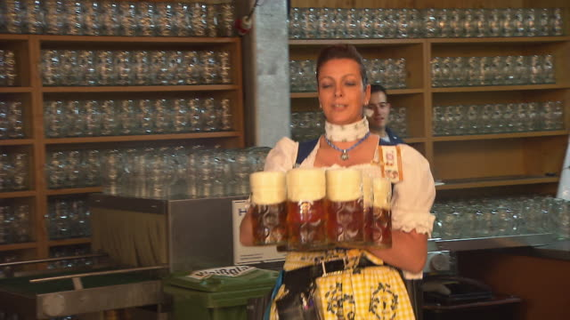 waitress carries beer mugs