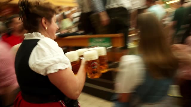 stockvideo's en b-roll-footage met waitress carries one liter mugs of beer in the armbrustschuetzenzelt tent on the opening day of the 2018 oktoberfest beer festival on september 22,... - carrying
