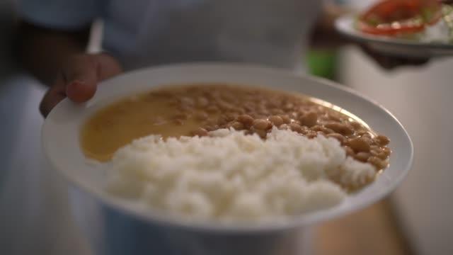 vídeos de stock, filmes e b-roll de garçonete carregando um arroz fresco e comida de feijão - meal