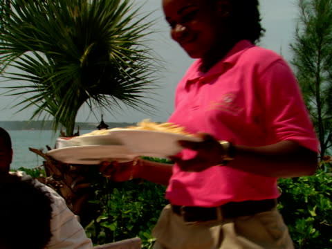 ms,  waitress carrying meals to family of four,  in outdoor restaurant,  harbour island,  bahamas - waitress stock videos & royalty-free footage