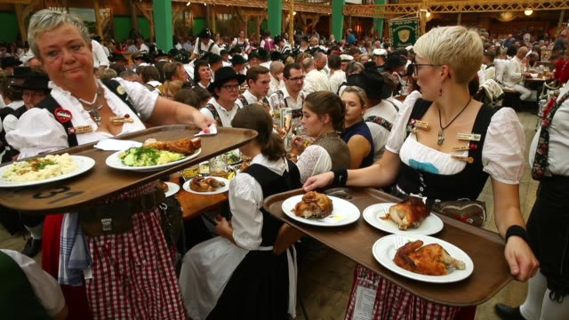 a waitress carrying plates of pork roast and grilled chicken makes her way among revelers in the schottemhamel tent on the opening day of the 2018... - oktoberfest stock videos & royalty-free footage