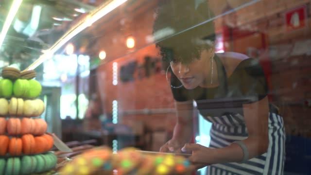 kellnerin überprüft süßigkeiten in einem feinkostladen - bäckerei stock-videos und b-roll-filmmaterial