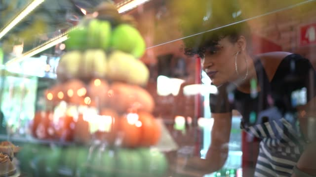 デリカテッセンで展示されているお菓子をチェックするウェイトレス - デリカッセン点の映像素材/bロール