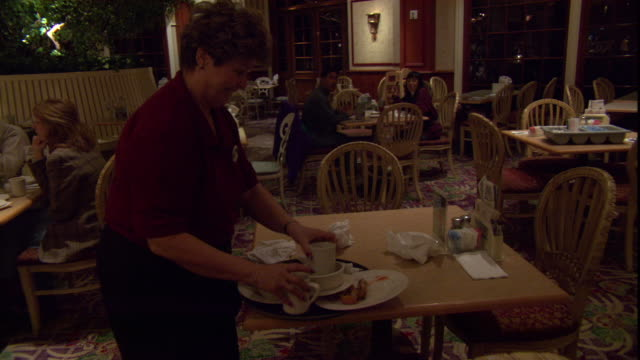 a waitress clears a table at a restaurant. - table stock videos & royalty-free footage