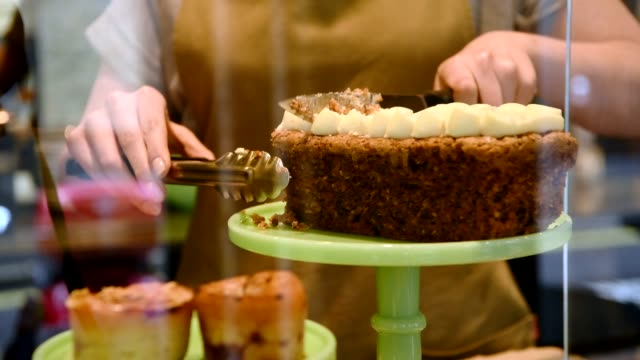Waitress cutting slice of cake on cake stand close up