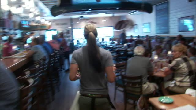 vídeos de stock e filmes b-roll de a waitress delivers food orders to saloon patrons. - empregada de mesa