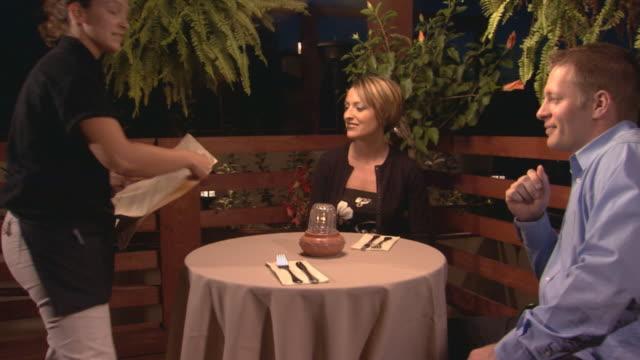 waitress giving menu's to couple at restaurant - 男性と複数の女性点の映像素材/bロール