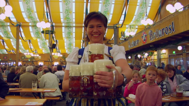 ms waitress in traditional clothes serving beer mugs, oktoberfest, munich, germany - tradition stock videos & royalty-free footage