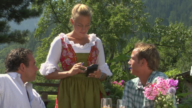 ms pan waitress in traditional dirndl dress talking to two men drinking beer in bavarian landscape, bavaria, germany - paying restaurant stock videos & royalty-free footage
