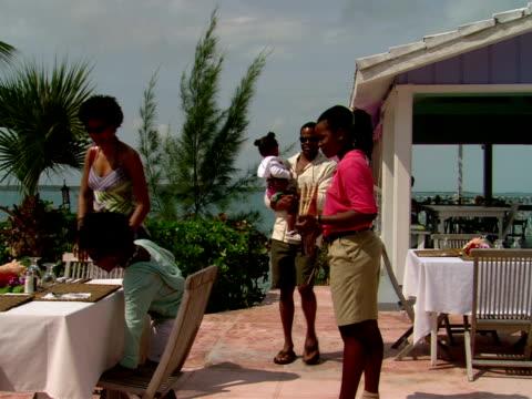 vídeos y material grabado en eventos de stock de ms,  waitress leading family of four to outdoor table in restaurant,  harbour island,  bahamas - palmera abanico