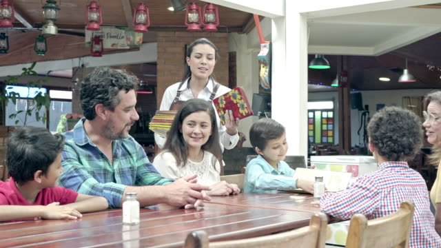 waitress offering the menu to the family to ask for their orders - 25 29 years stock videos & royalty-free footage