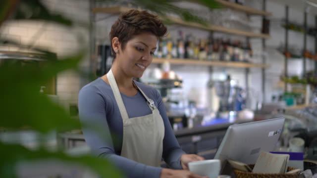servitrisen organisera en hylla och sedan gå och titta på systemet - servitris bildbanksvideor och videomaterial från bakom kulisserna