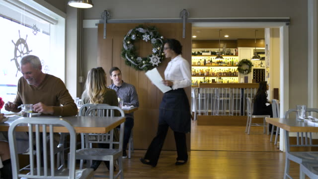 waitress passing menus to a young couple - grandangolo tecnica fotografica video stock e b–roll