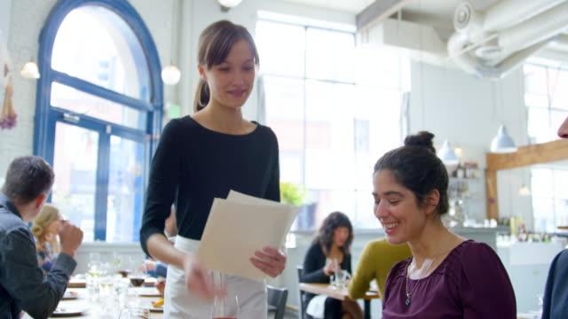 vídeos de stock e filmes b-roll de ms r/f pan td waitress passing menus to couples dining together in restaurant - empregada de mesa