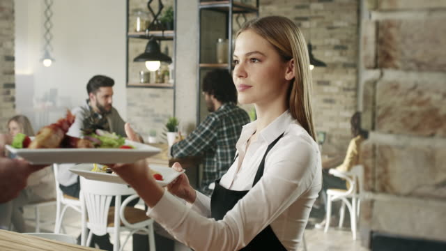 waitress picking up food from the kitchen - offrire un servizio video stock e b–roll