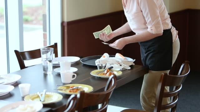 vídeos de stock e filmes b-roll de waitress picking up her tip, clearing table - empregada de mesa