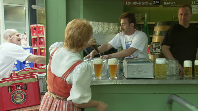 ms pan ws waitress pouring beer from bottle and walking through beer garden, viktualienmarkt, munich, bavaria, germany - waitress stock videos & royalty-free footage