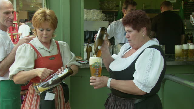 ms pan waitress pouring beer from bottle at beer garden, viktualienmarkt, munich, bavaria, germany - waitress stock videos & royalty-free footage