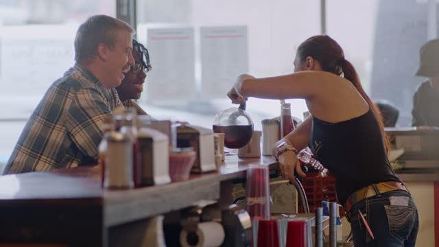 vídeos de stock e filmes b-roll de waitress pours coffee into coffee cups for young couple at an authentic diner counter - empregada de mesa