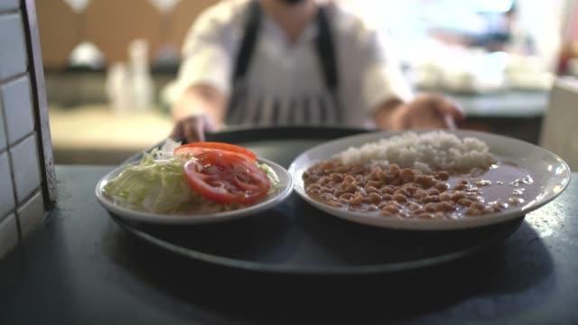 vídeos de stock, filmes e b-roll de garçonete recebendo um arroz fresco e comida de feijão - meal