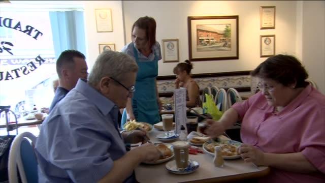 vídeos y material grabado en eventos de stock de waitress serves plate of fish and chips, man squeezes on tomato sauce - rebozado