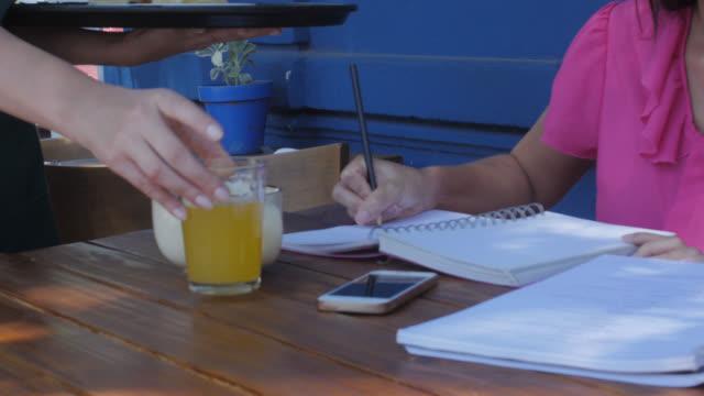 servitrisen serverar en trevlig asiatisk kvinna som arbetar på hennes anteckningsbok - servitris bildbanksvideor och videomaterial från bakom kulisserna