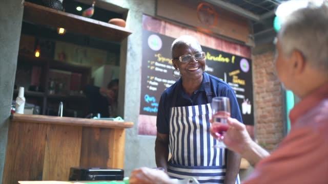 vídeos de stock e filmes b-roll de waitress serving a glass of wine to a customer in a restaurant - empregada de mesa