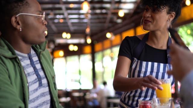 vídeos de stock, filmes e b-roll de empregada de mesa que serve o pequeno almoço a um grupo de amigos em um bar - garçom