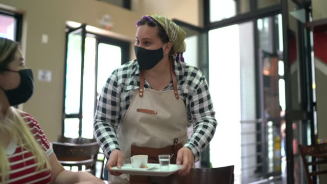 waitress serving coffee to a customer in a coffee shop - wearing face mask - serving size stock videos & royalty-free footage