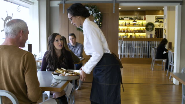 Waitress serving food to a mature couple