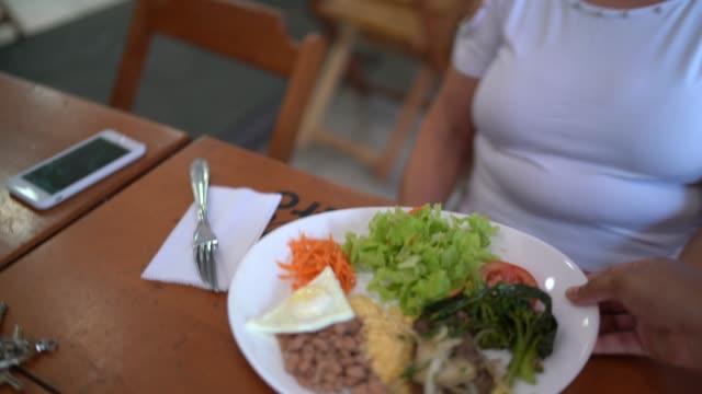 レストランで先輩女性にランチを提供するウェイトレス - ウェイトレス点の映像素材/bロール