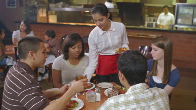 ms pan zi waitress serving meal to group of teens in restaurant and then walking away / san antonio, texas, usa - jugendalter stock-videos und b-roll-filmmaterial