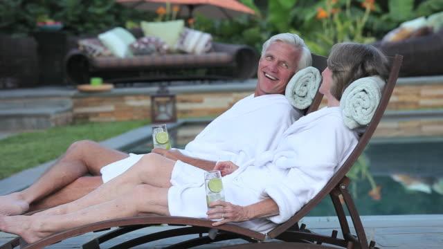 vidéos et rushes de ms tu waitress serving refreshments to senior couple relaxing by pool / richmond, virginia, usa - spa