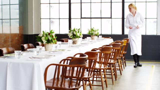 ms waitress setting banquet table for dinner party in loft - servitris bildbanksvideor och videomaterial från bakom kulisserna