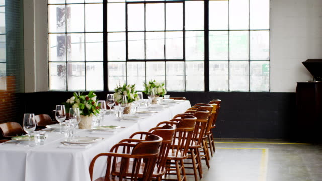 MS waitress setting banquet table for dinner party in loft