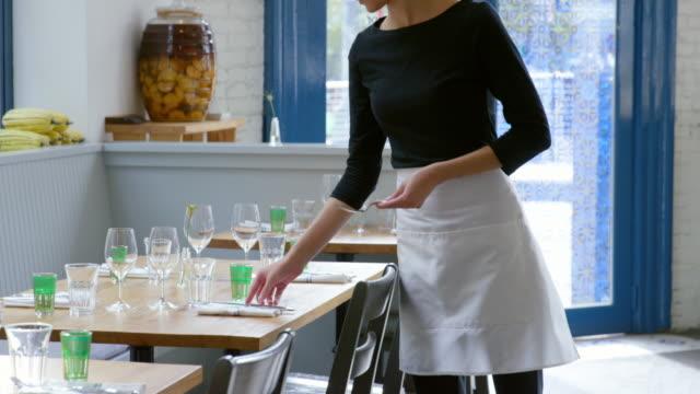 MS TU waitress setting table in dining room of restaurant