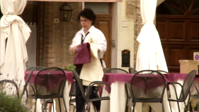 a waitress spreads tablecloths on tables at an outdoor cafe in montepulciano, italy. available in hd. - tischtuch stock-videos und b-roll-filmmaterial