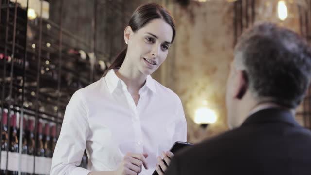 waitress taking food order on digital device in restaurant - 注文する点の映像素材/bロール
