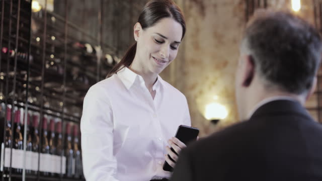 Waitress taking food order on digital device in restaurant